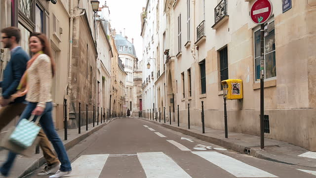young couple walking with shopping bags smile at each other as they cross a paris street. - vicolo video stock e b–roll