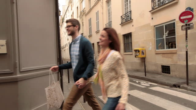 Young couple walking with shopping bags smile at each other as they cross a Paris street.