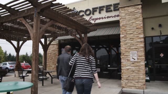 a young couple walks through the door of a coffee shop - building entrance stock videos & royalty-free footage