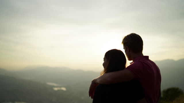 Young couple watch sunset over mountains overlooking lake