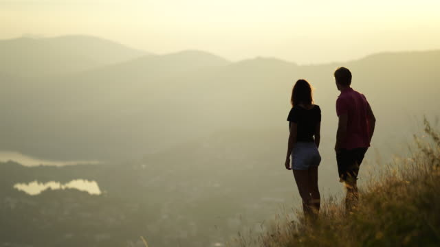 young couple watch sunset over mountains overlooking lake - adventure stock videos & royalty-free footage