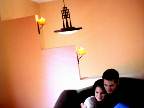 vídeos de stock e filmes b-roll de overexposed canted young couple watch television, laugh + look shocked / modern decor with candles - super exposto