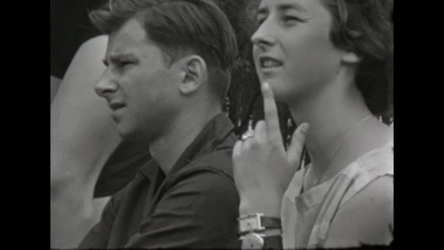 a young couple watches something interesting outdoors / shot in 1957 - teenage girls stock videos & royalty-free footage