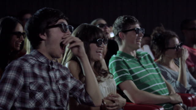 vídeos de stock, filmes e b-roll de young couple watching 3d movie at the movie theater - óculos de terceira dimensão