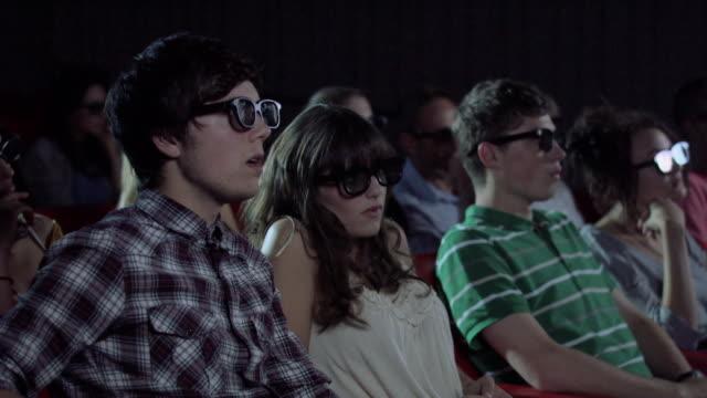 vídeos de stock, filmes e b-roll de young couple watching 3d movie at the movie theater - óculos de terceira dimensão