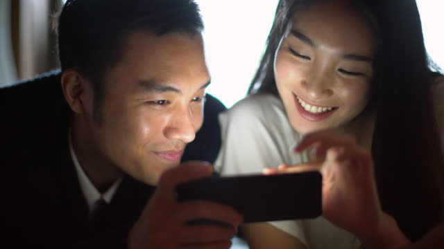 MS young couple watching a movie on their smartphone together.