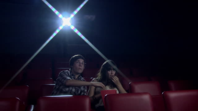 Young couple watching movie at the movie theater