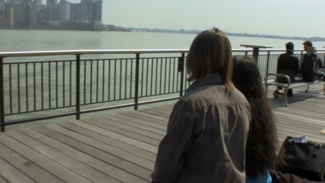 MS ZI ZO PAN Young couple watching New York city skyline from New Jersey pier / Jersey City, New Jersey, USA