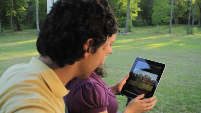 cu young couple watching pictures on digital tablet outdoors / madison, florida, usa - couple relationship photos stock videos & royalty-free footage