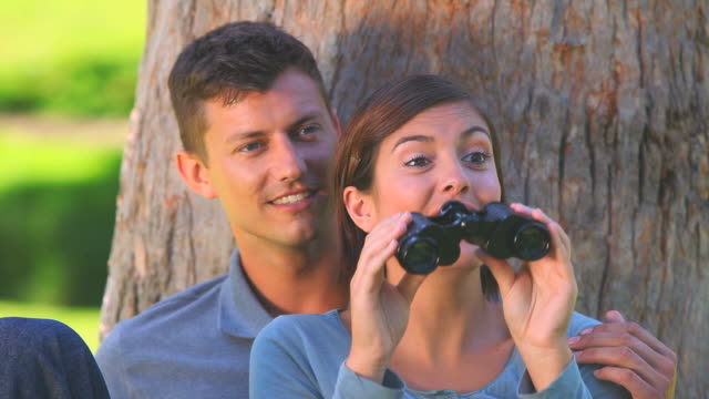 stockvideo's en b-roll-footage met young couple watching something through binoculars / cape town, western cape, south africa - verrekijker