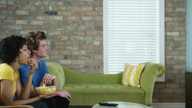 young couple watching television on a flat screen as they eat a bowl of popcorn - entertainment center stock videos and b-roll footage