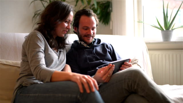 DOLLY: Young couple watching TV on tablet computer