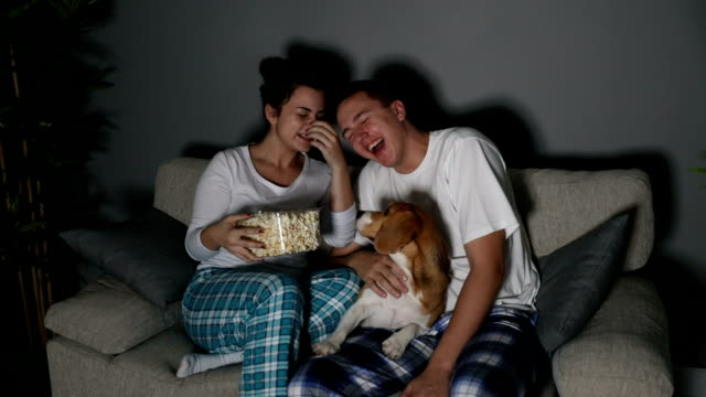 young couple watching tv together - pyjamas stock videos & royalty-free footage