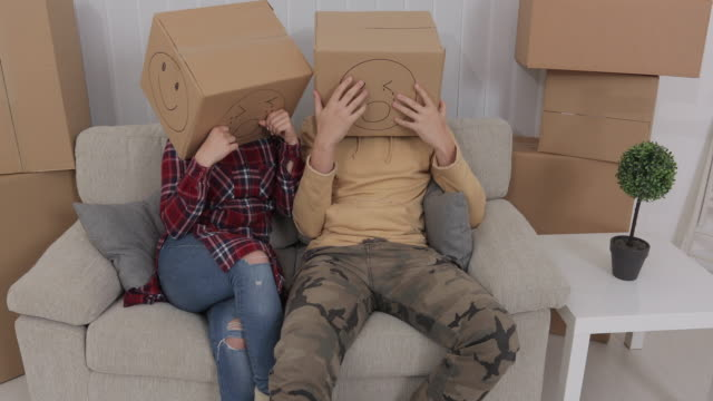 Young couple wearing emoticon boxes on heads...