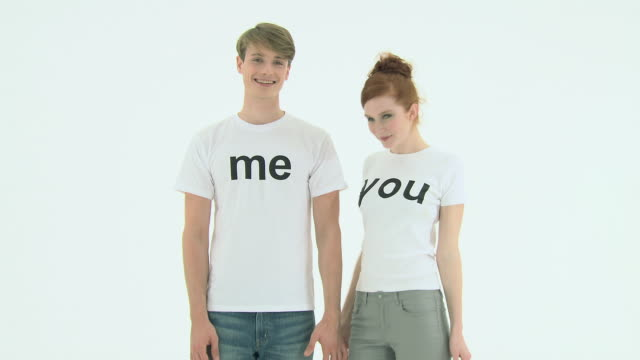 Young couple wearing t-shirts that say me and you, zoom out