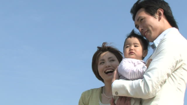 young couple with baby against blue sky - 両親点の映像素材/bロール