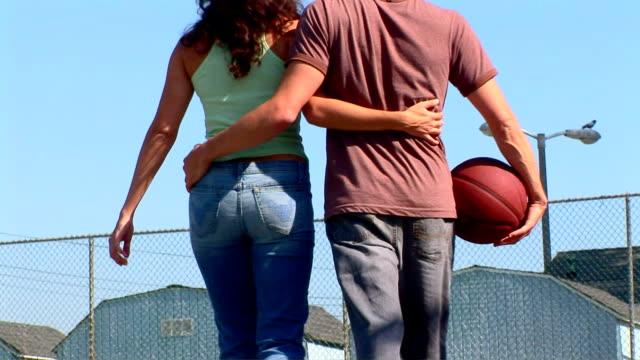 vídeos de stock, filmes e b-roll de young couple with basketball - de braços dados