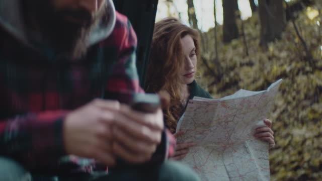 Unga par med uppdelning bil i skogen