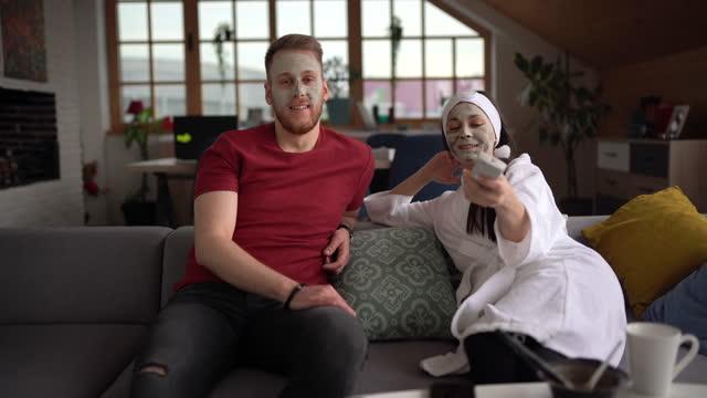vidéos et rushes de jeune couples avec le masque d'argile détendant à la maison - boyfriend