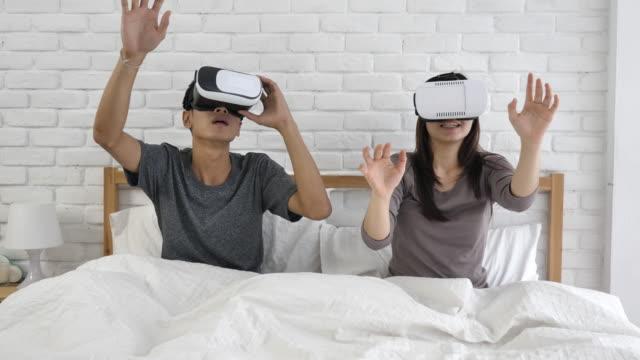 vídeos y material grabado en eventos de stock de joven pareja con gafas de realidad virtual en la cama - two dimensional shape