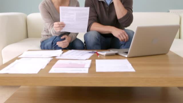 vídeos de stock e filmes b-roll de young couple with paperwork on the phone - telefone sem fio