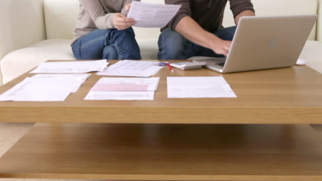 young couple with paperwork using laptop - 金銭に関係ある物点の映像素材/bロール