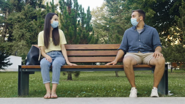 slo mo young couple with protective face masks spreading hands while sitting on the bench in public park - 30 seconds or greater stock videos & royalty-free footage