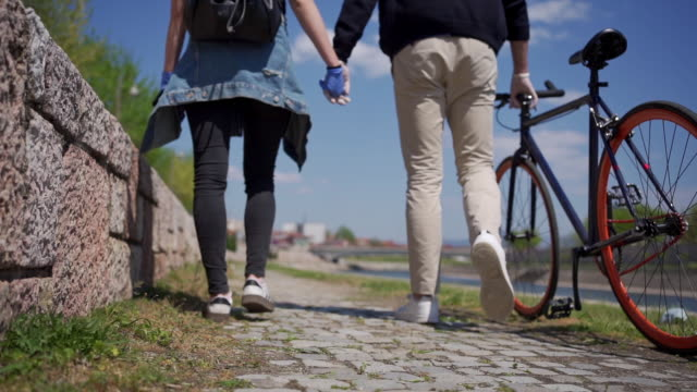 young couple with protective gloves holding hands and walking by the river - glove stock videos & royalty-free footage