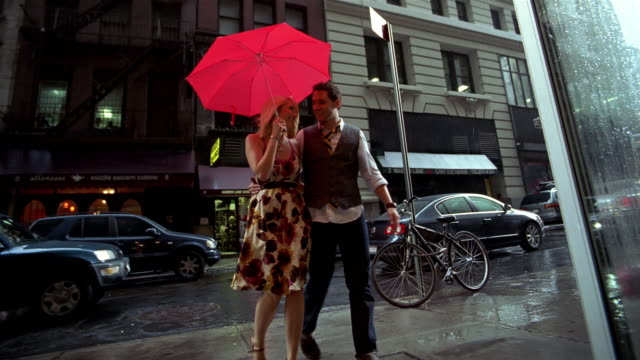 vídeos y material grabado en eventos de stock de slo mo, ms, la, young couple with red umbrella crossing street in rain, new york city, new york, usa - cruzar