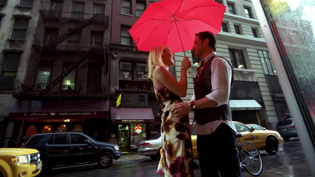 SLO MO, MS, LA, Young couple with red umbrella crossing street in rain, New York City, New York, USA