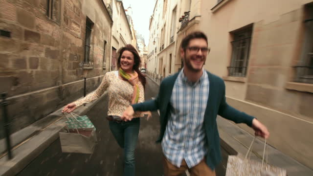 MEDIUM TRACKING SHOT couple holding hands  and carrying shopping bags runs toward camera in alley in Paris