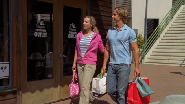 SLO MO, MS, DS, Young couple with shopping bags walking on street, Morro Bay, California, USA,