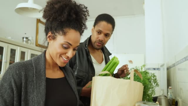 Jeune couple avec shopping dans cuisine