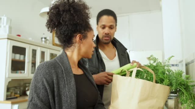 young couple with shopping in kitchen - unpacking stock videos & royalty-free footage