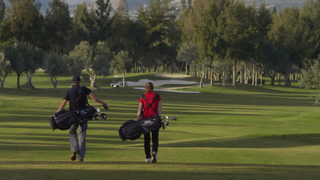 LS young couple with their golf bags slung over their shoulders walking along fairway in last afternoon,light, rear view, RED R3D 4K