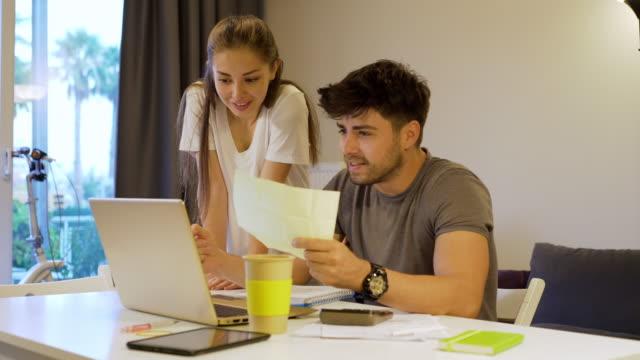 vidéos et rushes de jeunes couples travaillant à la maison - hot desking
