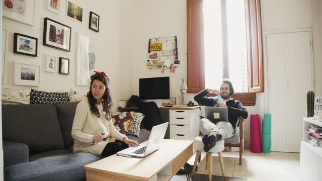 vídeos de stock e filmes b-roll de young couple working from home - interior de casa