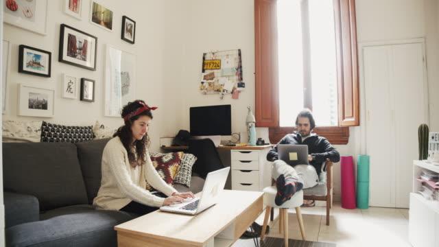 vidéos et rushes de jeune couples travaillant de la maison - appartement