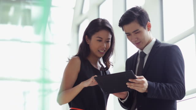 MS young couple working on a digital tablet in modern office.