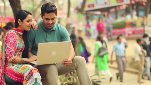 young couple working on a laptop, suraj kund fair, faridabad, haryana, india - online shopping stock videos & royalty-free footage
