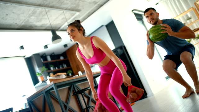 vídeos y material grabado en eventos de stock de una joven pareja haciendo ejercicio en casa. - refugiarse en un lugar concepto