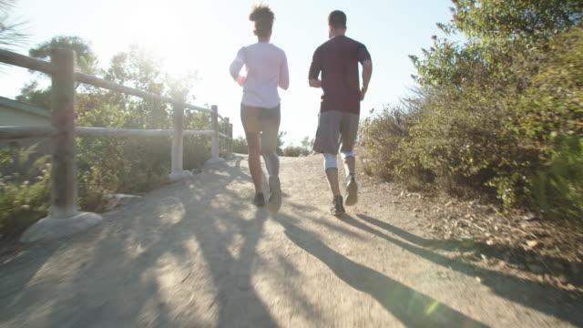 vidéos et rushes de young couple working out together outdoors - deux personnes