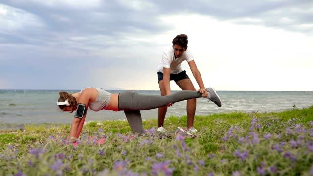 vídeos de stock, filmes e b-roll de jovem casal treinamento treino na praia - embrace