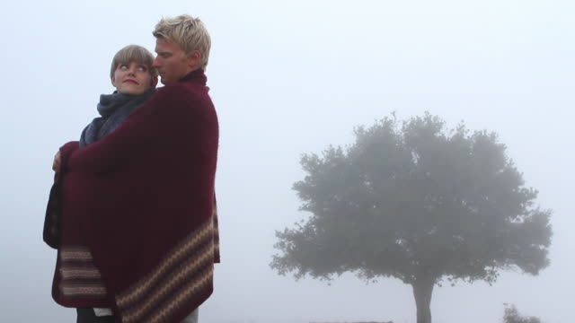 MS Young couple wrapped in blanket / Big Sur, California, USA
