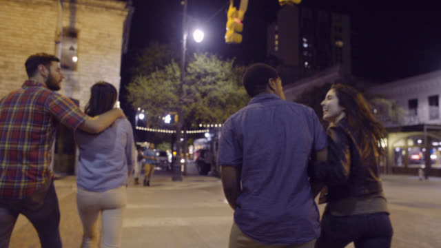 Young couples cross streets together walking through downtown Austin, Texas at night