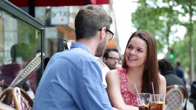vidéos et rushes de young couples dine at quaint parisian sidewalk cafe. - voix