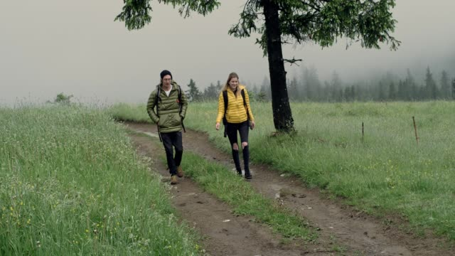 young couple's mountain adventure. foggy day - stivale video stock e b–roll