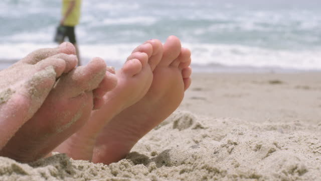 young couple's sandy feet on beach by the pacific ocean 4k - vesper stock stock videos & royalty-free footage