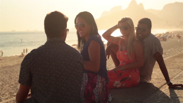 Young couples talk and laugh from boardwalk overlooking Ipanema Beach