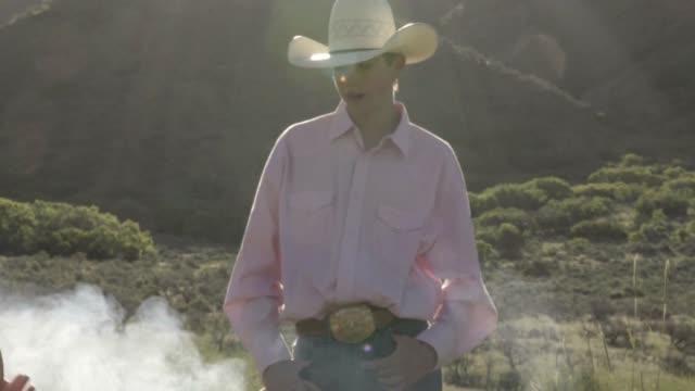 junger cowboy am lagerfeuer - ranch stock-videos und b-roll-filmmaterial